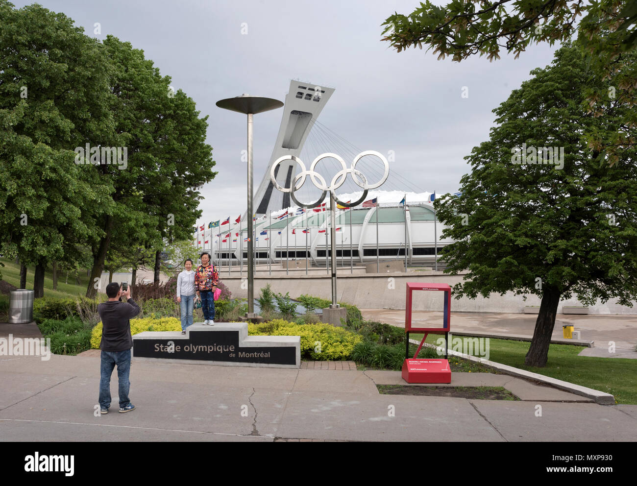 Tourists pose for a photograph at The Olympic Park, Montreal Canada. - Stock Image