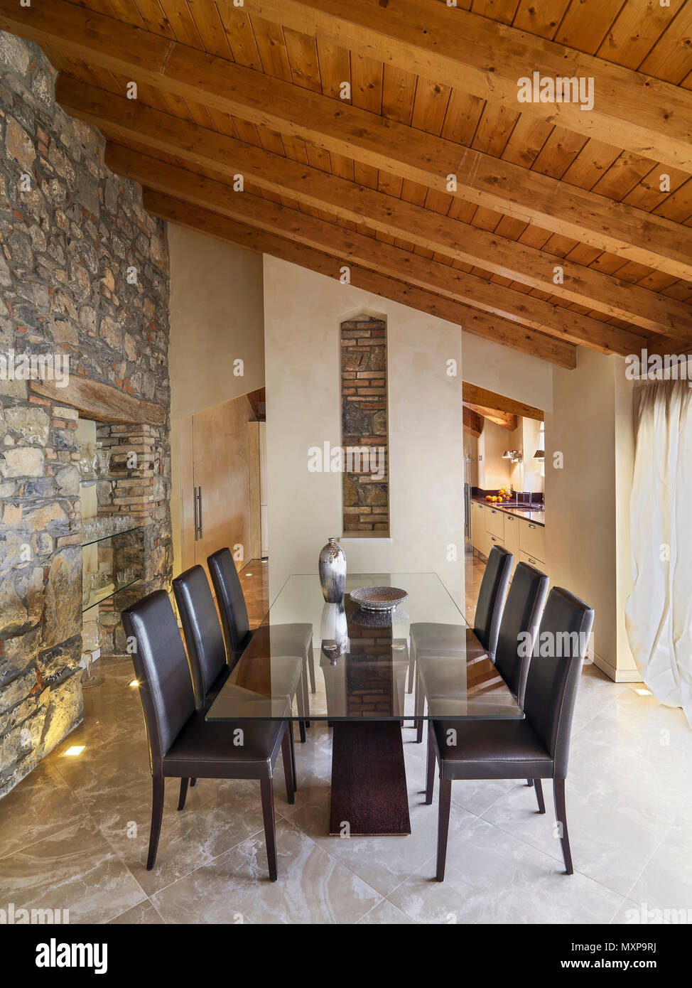 dining room interior in the foreground the glass dining table with brown leather chairs the floor and the wall are made of stone while the ceiling is  - Stock Image