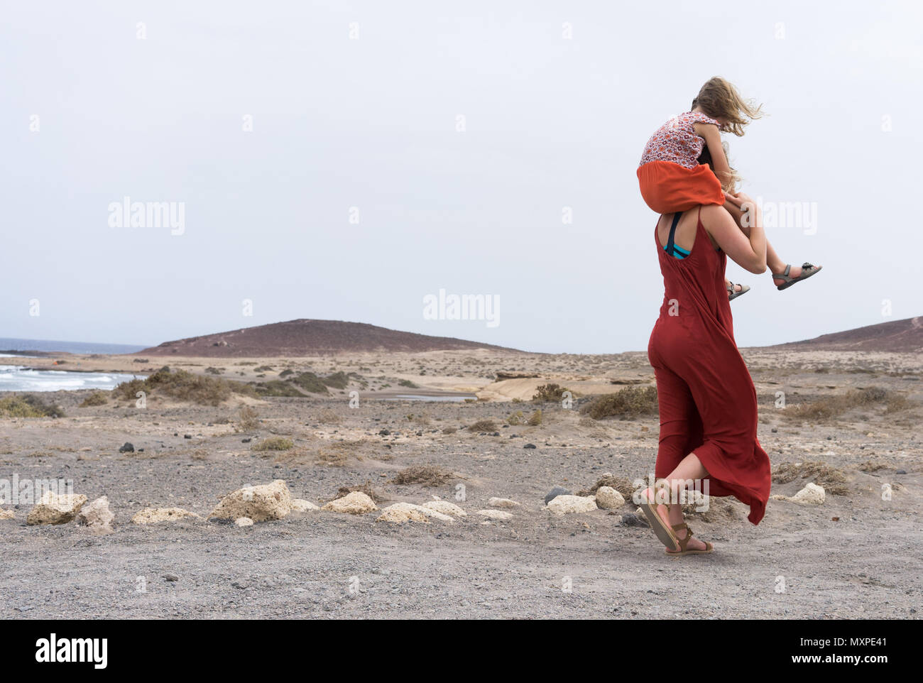 Mother carrying daughter on shoulders on rugged terrain by the beach - Stock Image