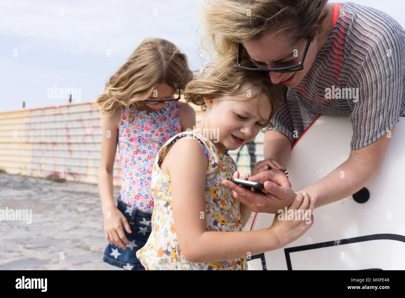 mother showing her daughter something on her mobile phone with the other daughter in the background - Stock Image
