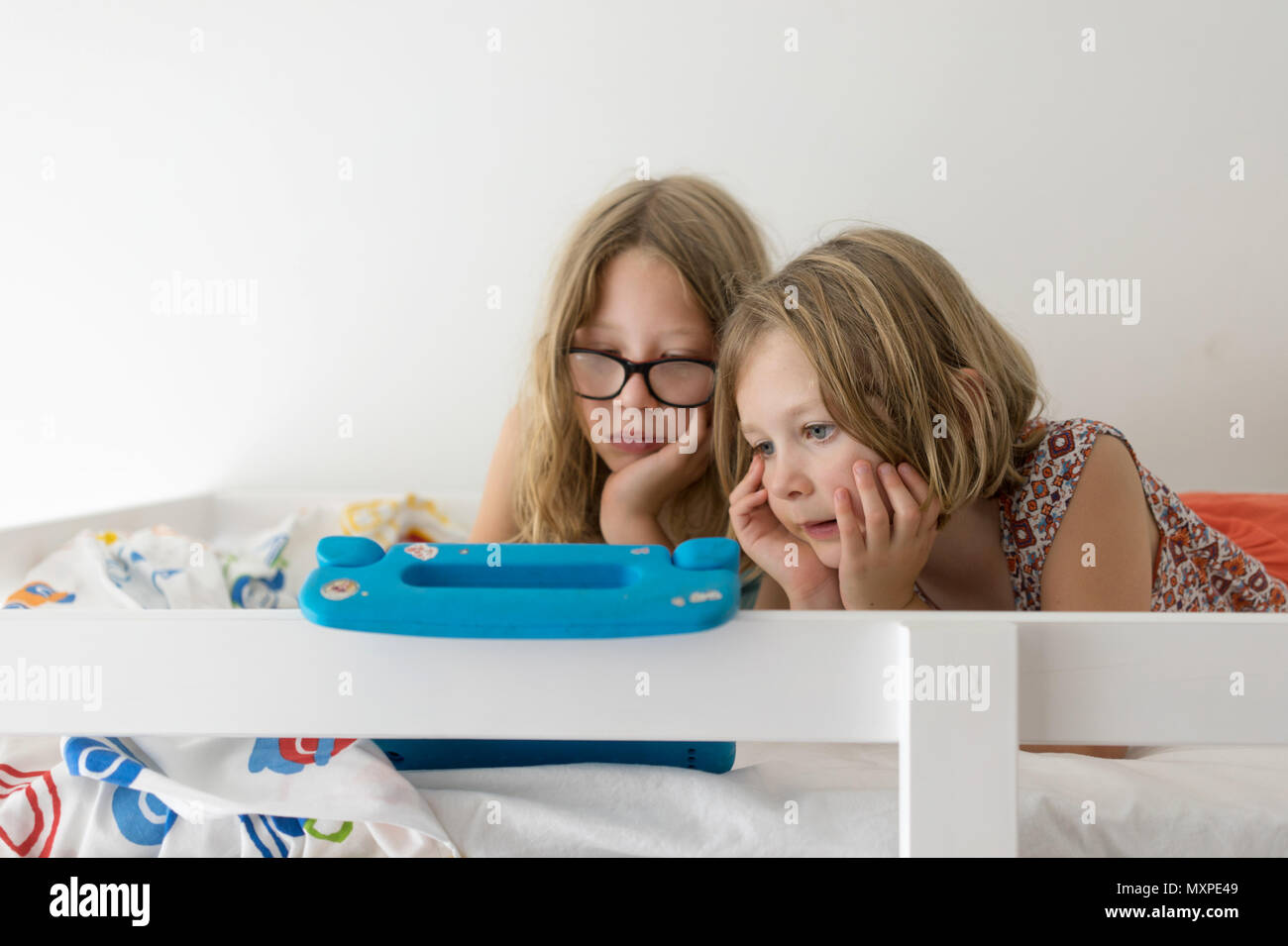 Two female children watching the tablet on the top bunk - Stock Image