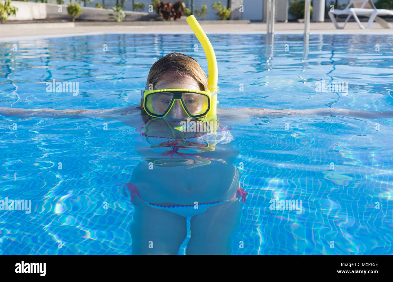 Woman in a swimming pool with a mask and snorkel on - Stock Image