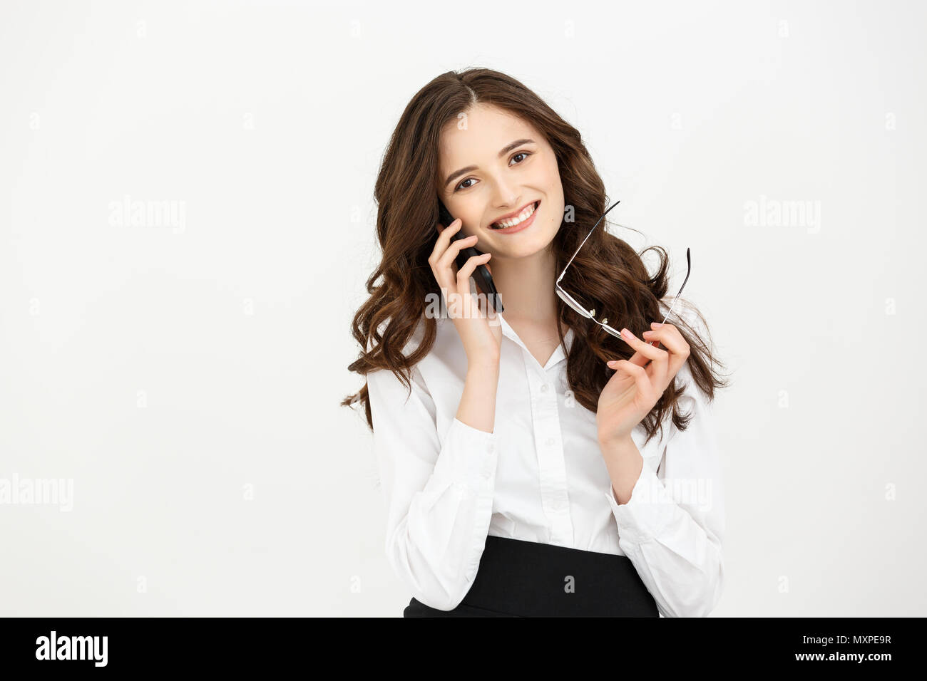 Thoughtful female student talking on mobile phone. Attractive business woman thinking about something during using cellphone. - Stock Image