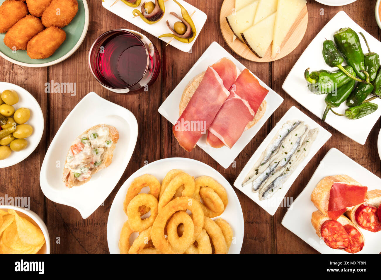 The food of Spain. An overhead photo of many different Spanish tapas, shot from above on a dark rustic texture. Jamon, cheese, wine, olives, croquette - Stock Image