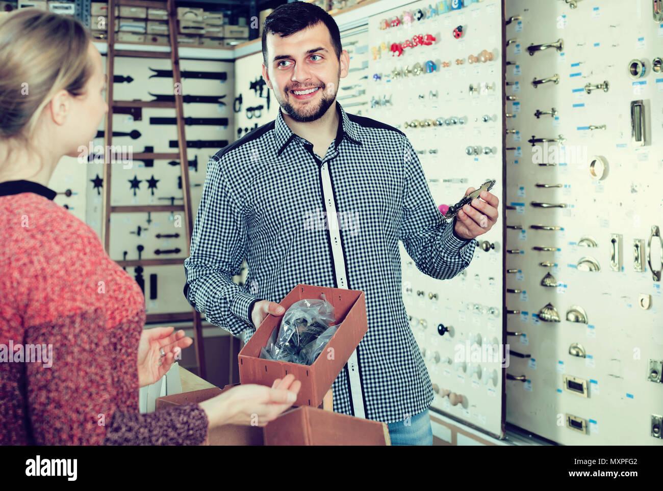 professional male seller assisting woman in choosing door handles in ...