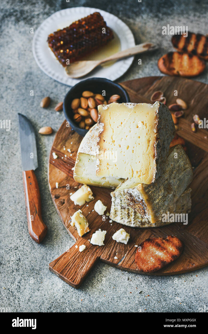 Cheese platter with cheese assortment, nuts, honey and bread - Stock Image