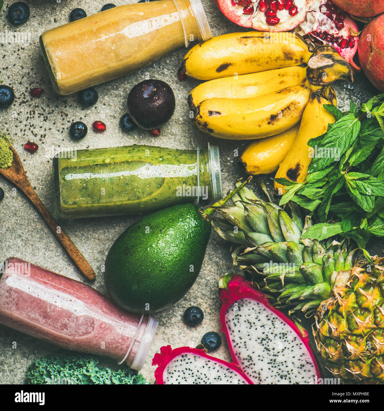 Colorful smoothies in bottles with fresh tropical fruit, square crop - Stock Image