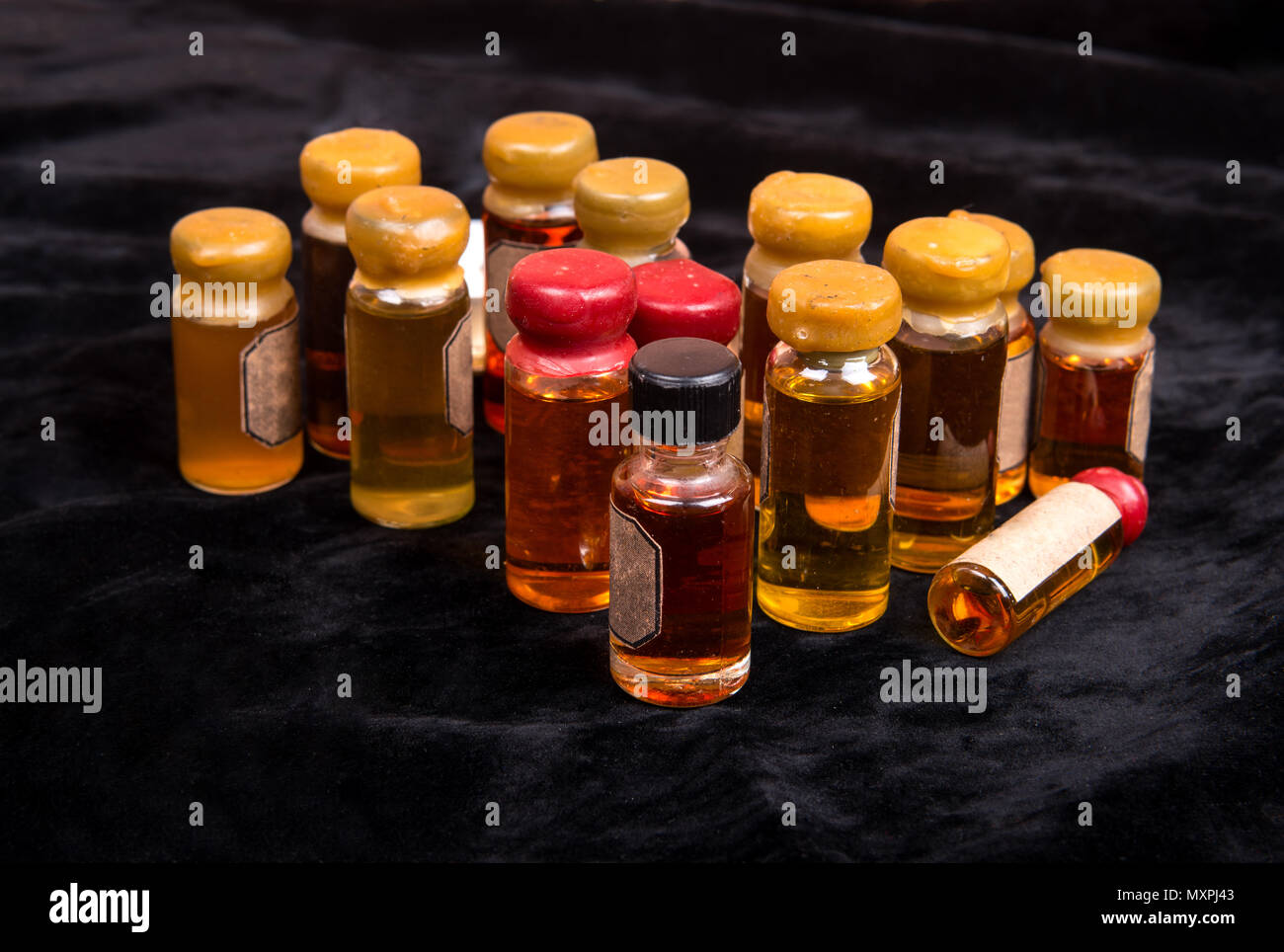 Numerous bottles of magical potion on dark background - Stock Image