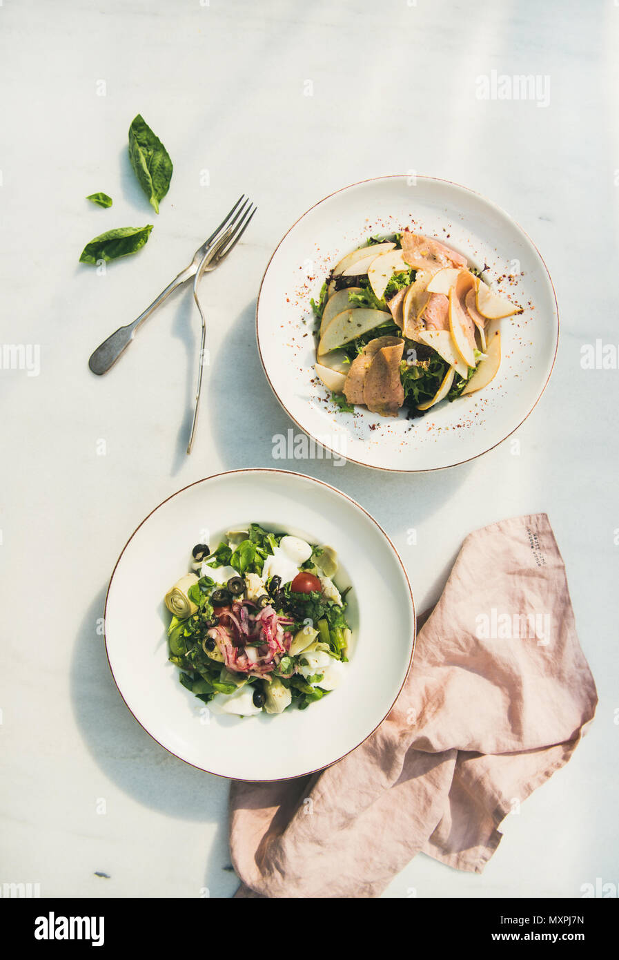 Fresh green summer salads in white plates, top view - Stock Image