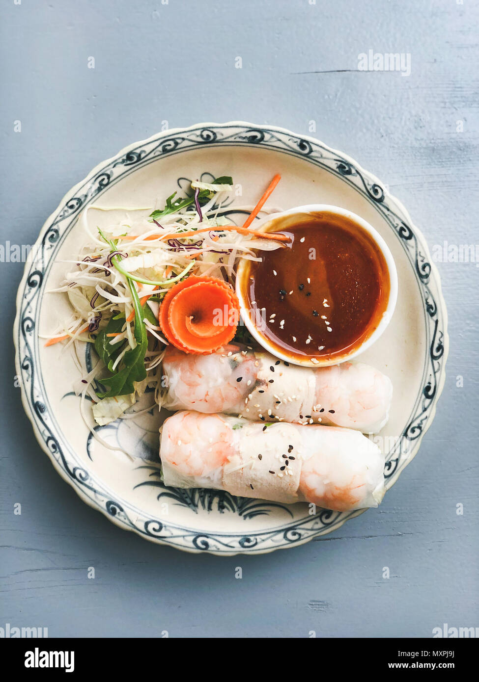 Asian style dinner. Flat-lay of steamed dumplings Dim sum and summer rice paper rolls with shrimp and sauce over blue table, top view, copy space. Chinese cuisine - Stock Image