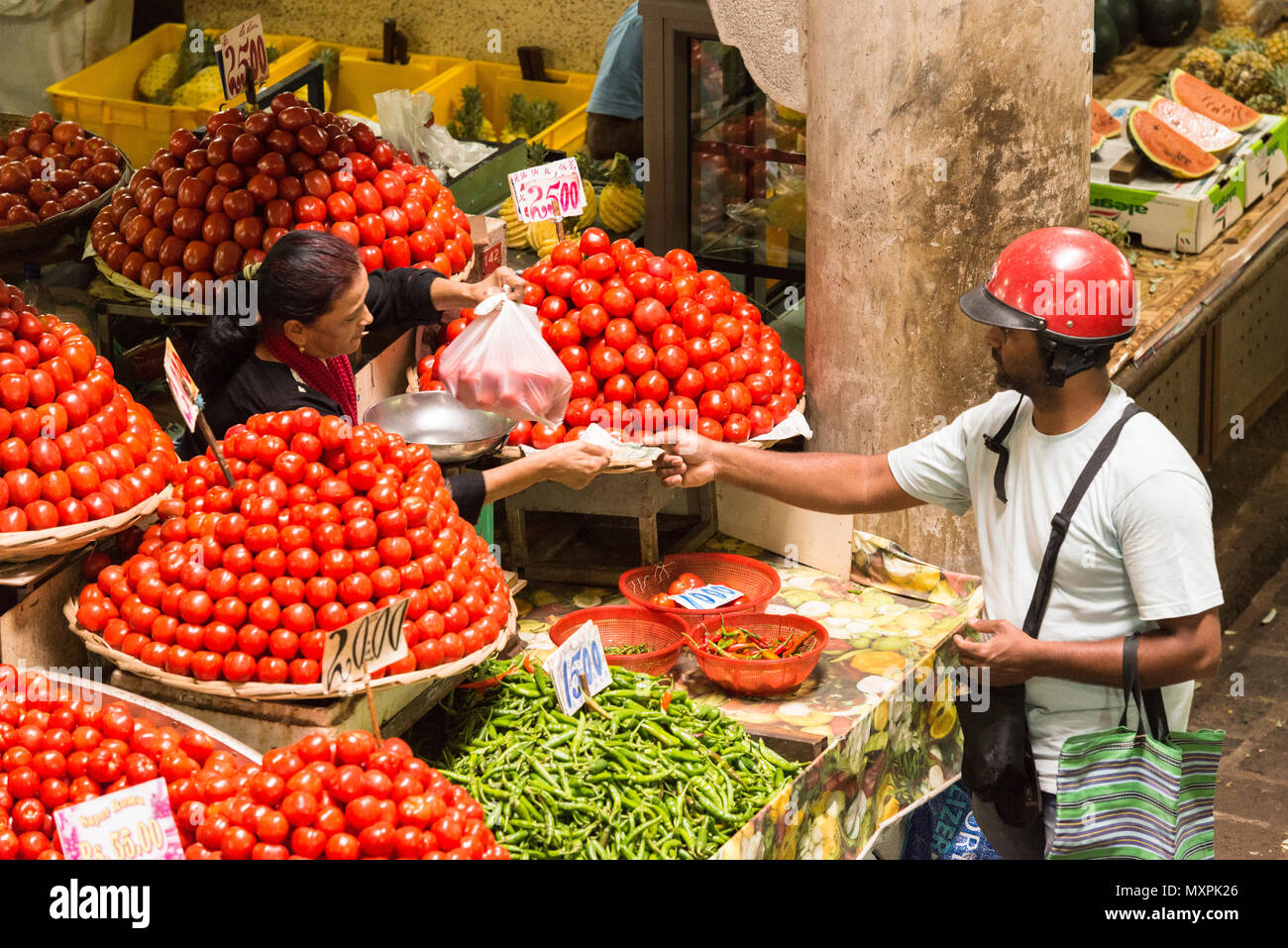 A customer in a motorcycle helmut paying for a plastic bag of tomatoes in the fruit and vegetable market, Port Louis, Mauritius Stock Photo