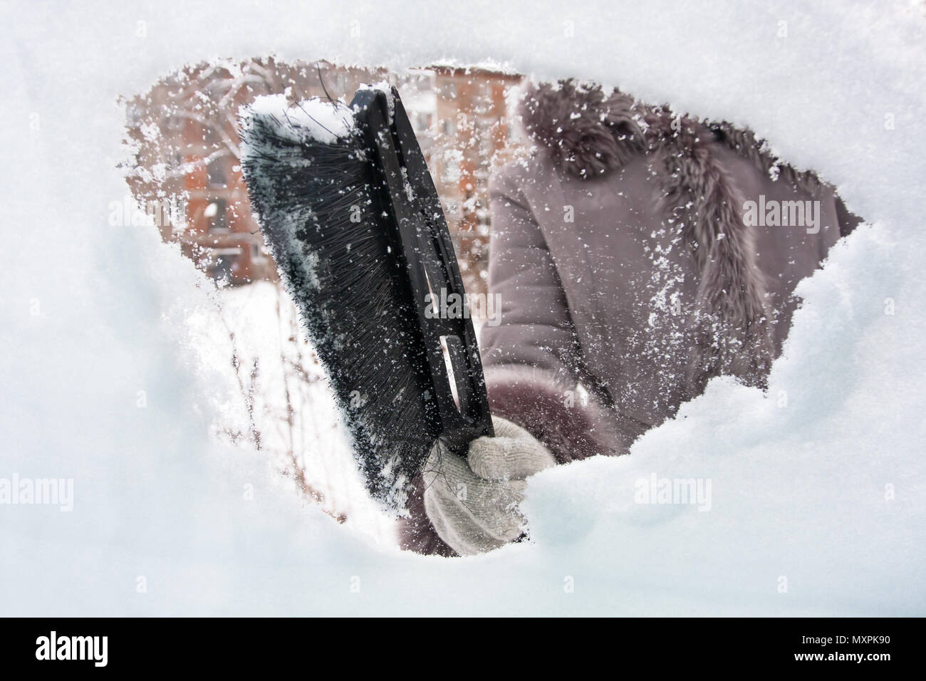 hand cleaning car from the snow with brush - Stock Image