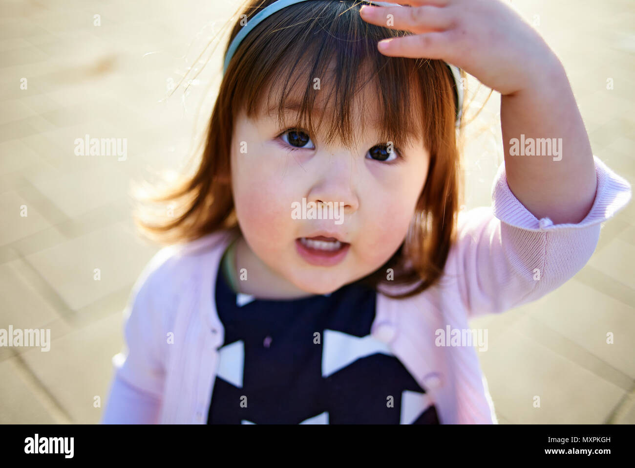 Portrait of a cute young Asian baby girl with rosey cheeks in cold weather looking into camera - Stock Image