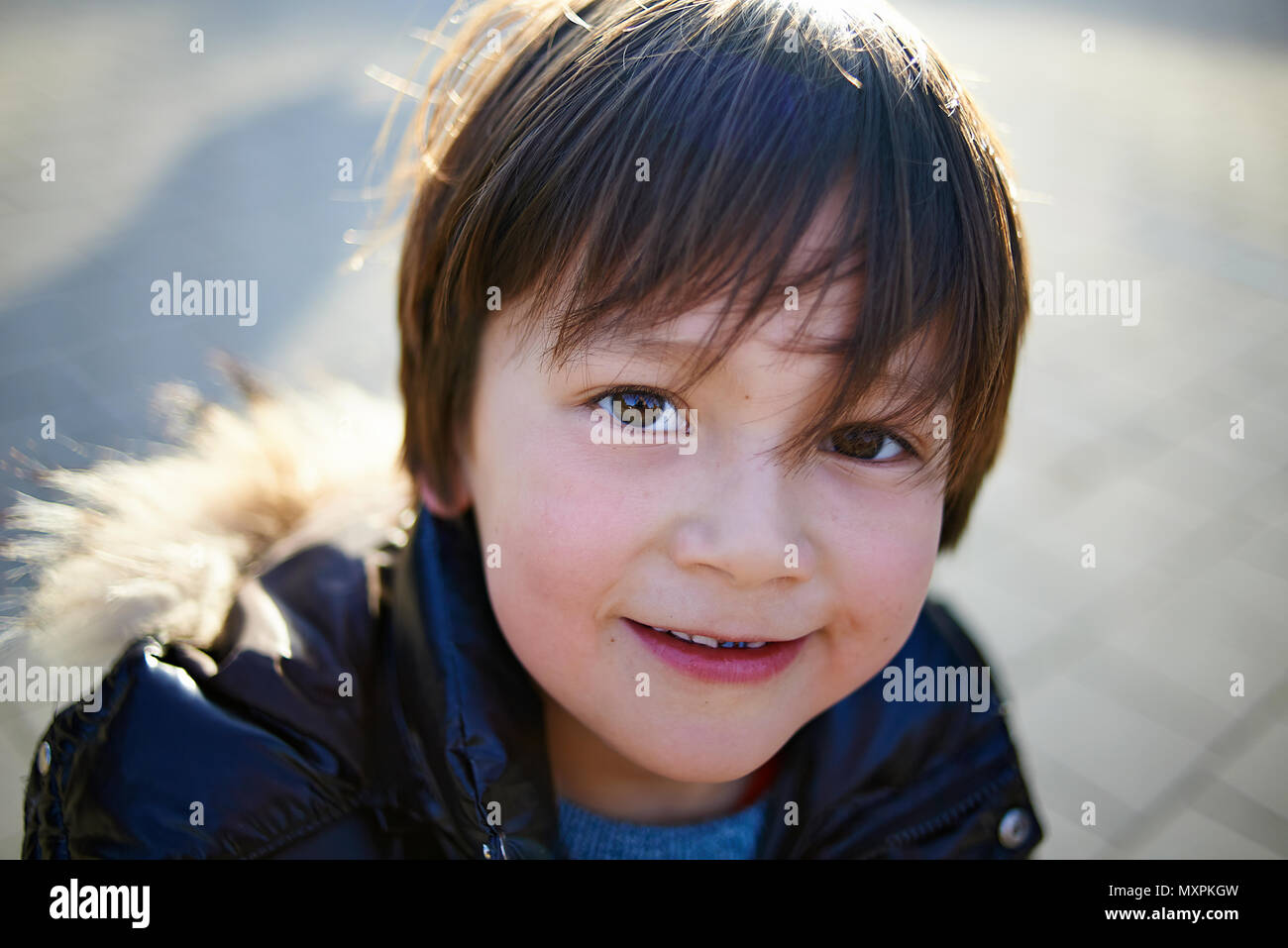 Portrait of a young preteen Japanese boy in autums sunshine at a school playground looking into camera - Stock Image