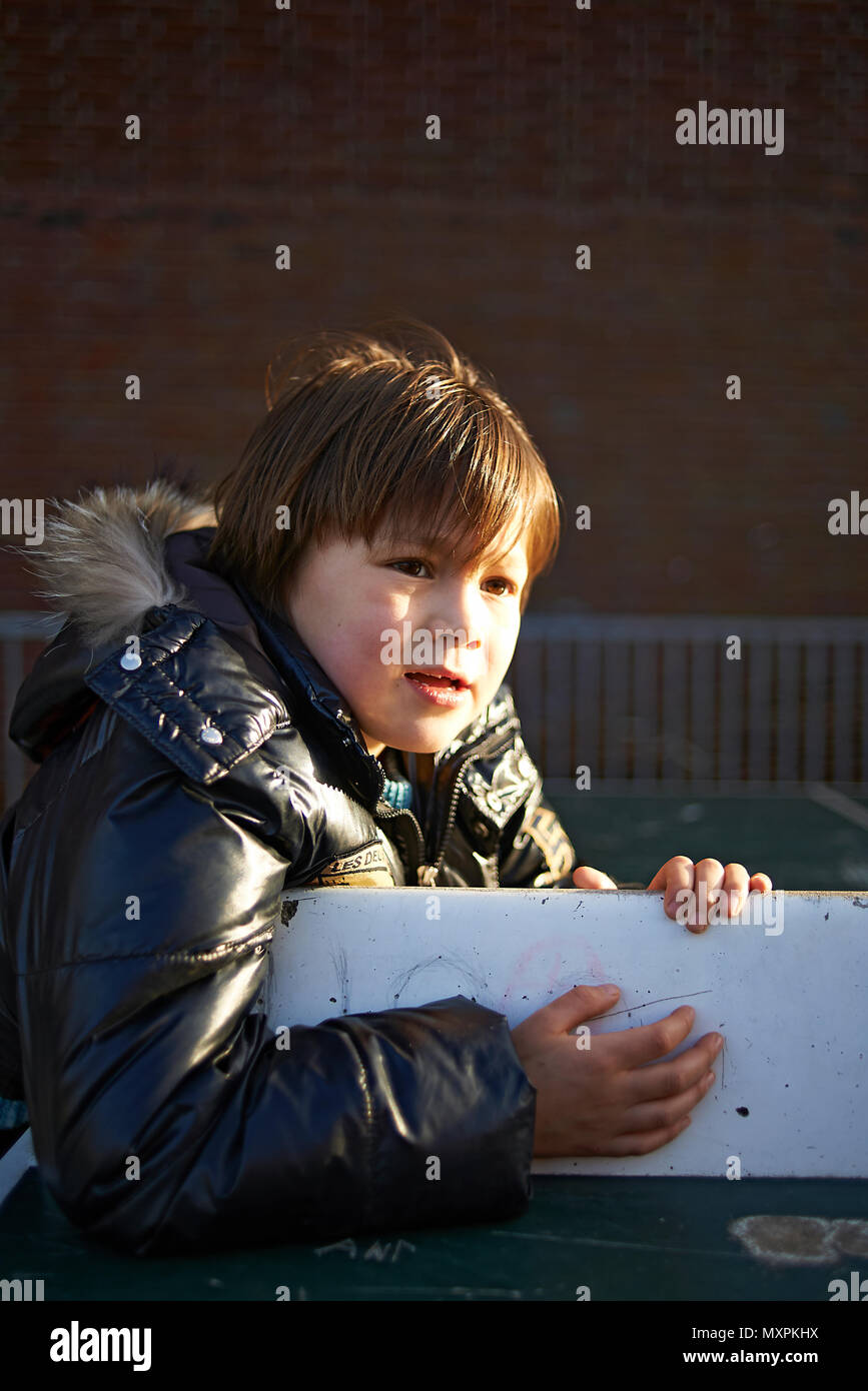 YOung Japanese boy wearing winter coat playing at the school playground in winter sunshine - Stock Image