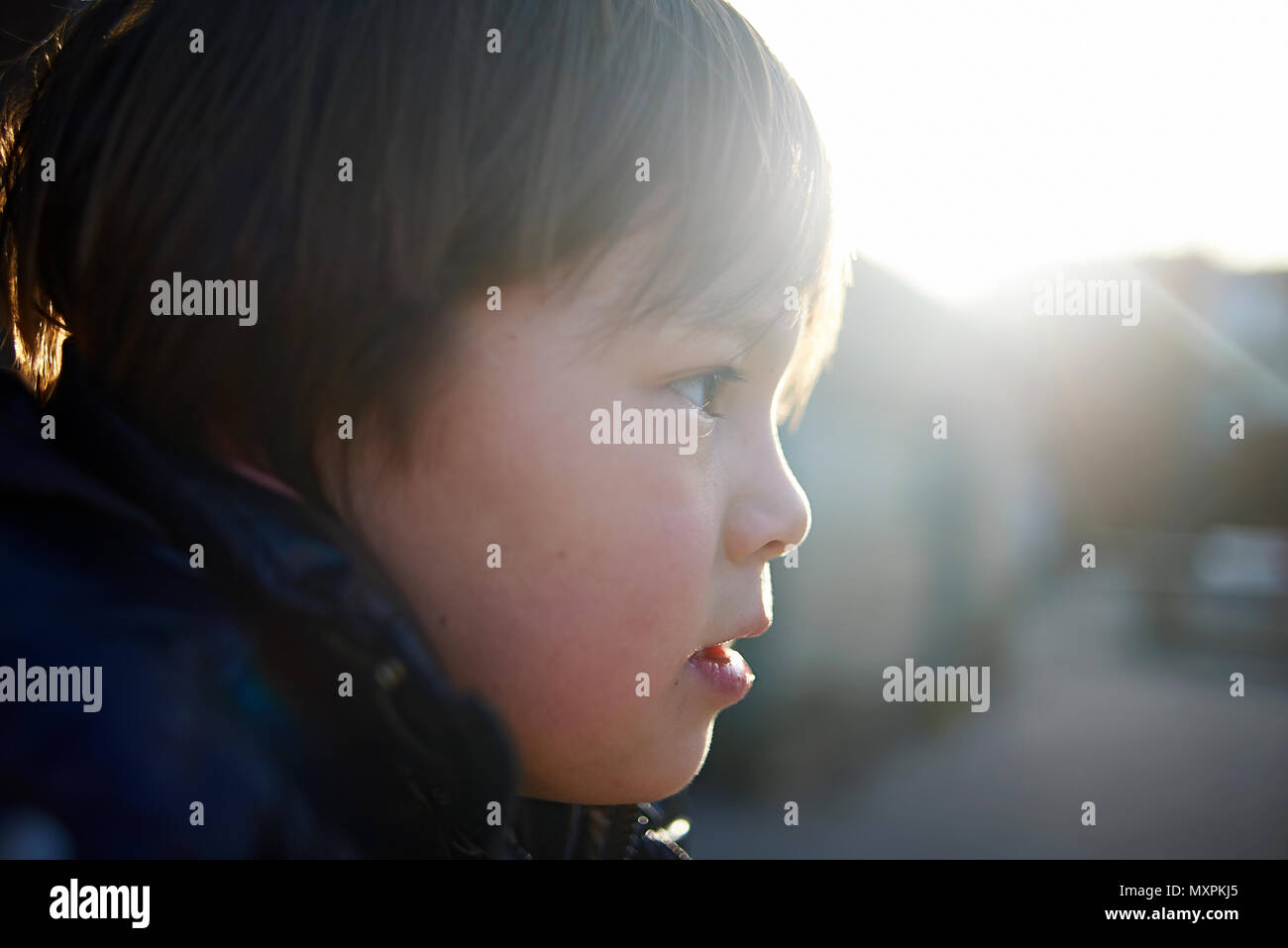 Side profile view of a young preteen Japanese boy in autums sunshine at a school playground - Stock Image