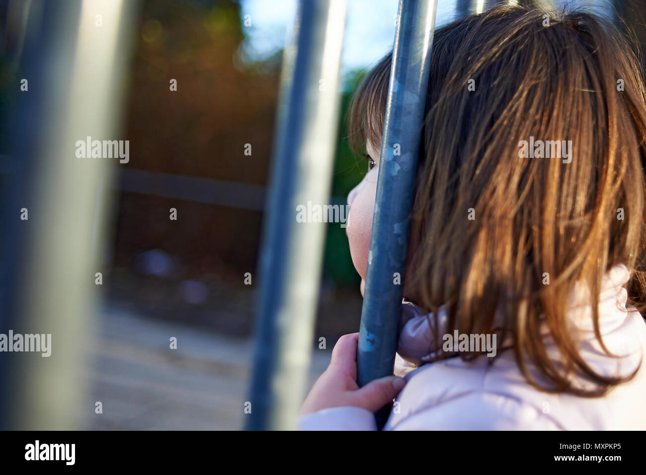 Cute Japanese baby girl sticking her head through some metal bars wanting to go out to play - Stock Image