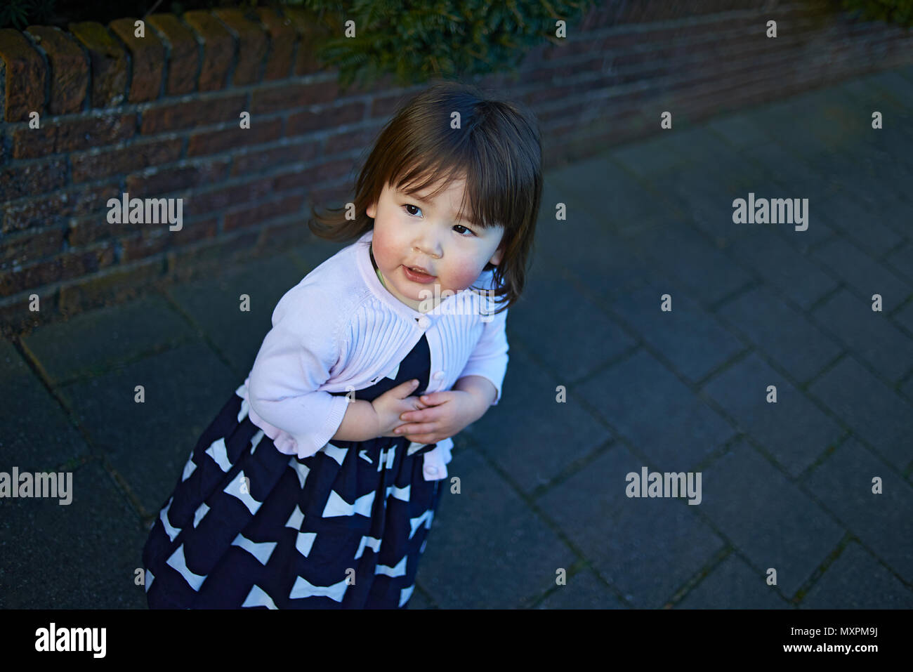 High angle shot of a cute Japanese baby girl standing alone on a paved path in the village Stock Photo