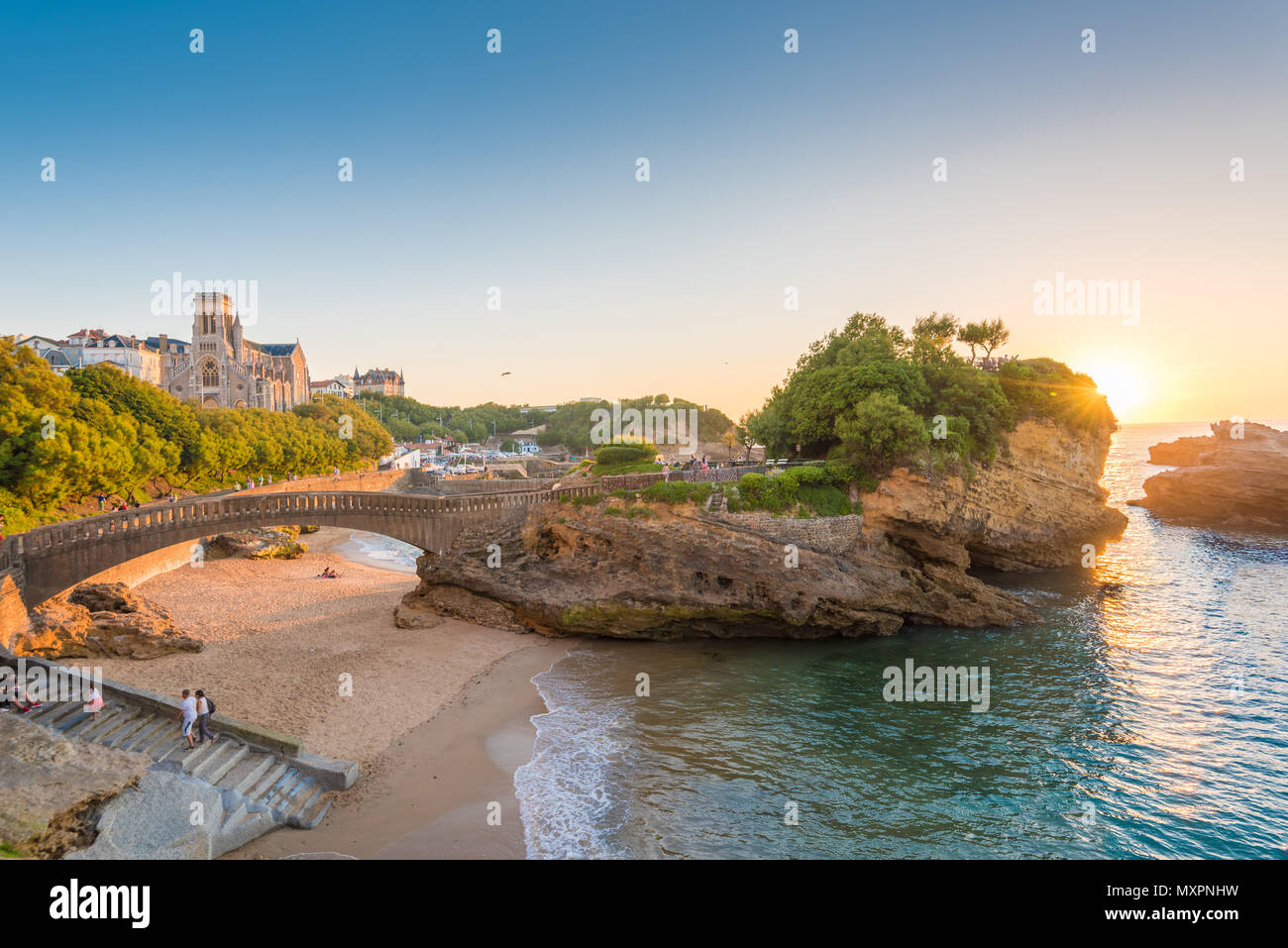Landscape in Biarritz, France and the sun setting in the horizon over the ocean Stock Photo