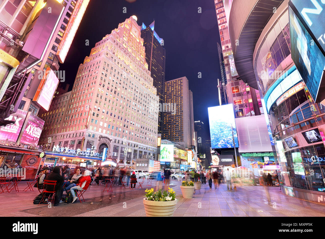 NEW YORK, USA - APRIL 12: The architecture of the famous Times Square in New York city, USA with its neon lights and panels at night and a lot of tour - Stock Image