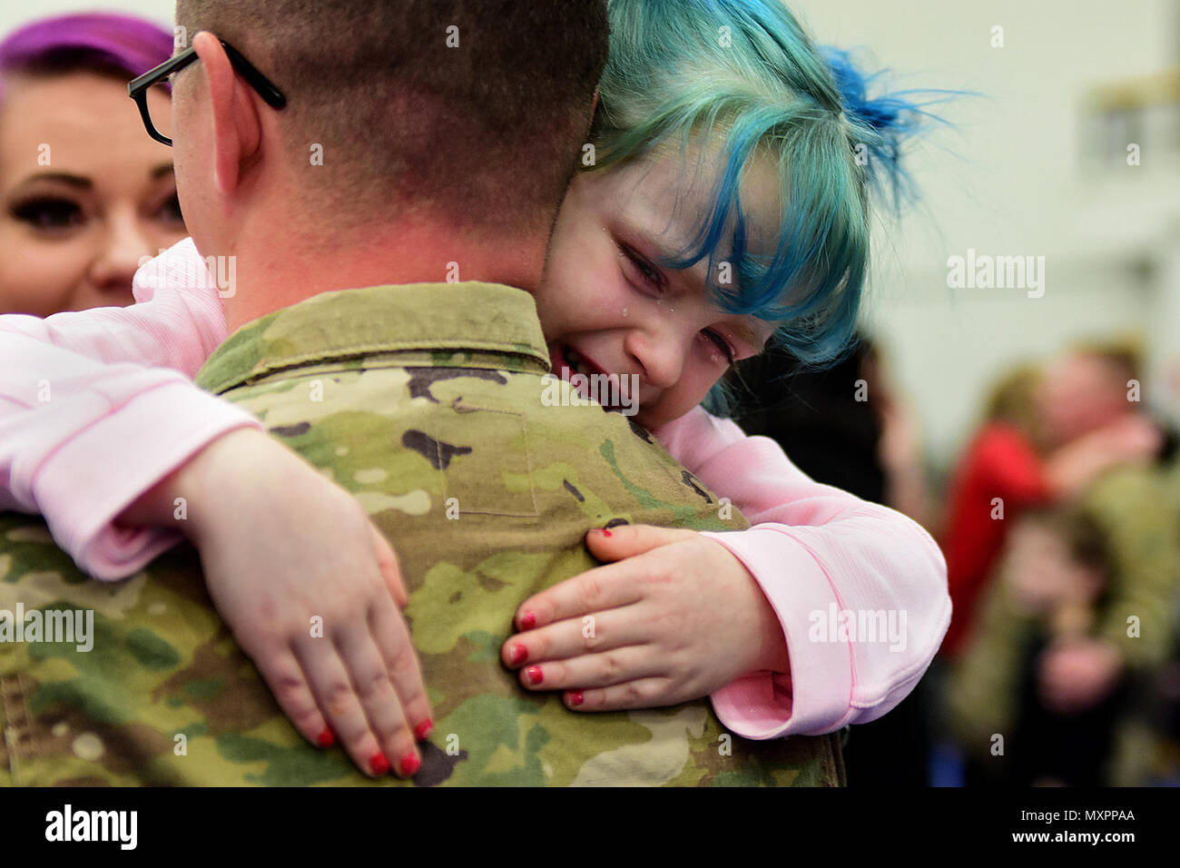 Six-year-old Rose Lowe greets her father, Sgt. Jonathan Lowe of the 109th Transportation Company, with a tearful hug Dec. 1 at Joint Base Elmendorf-Richardson's Buckner Physical Fitness Center. The 109th, part of U.S. Army Alaska's 17th Combat Sustainment Support Battalion, deployed to Kuwait in March in support of Operation Inherent Resolve. (Army photo/John Pennell) - Stock Image