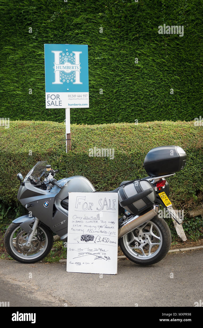 Two items for sale. House and BMW modern motor cycle promoted outside the property  on the roadside in England UK - Stock Image