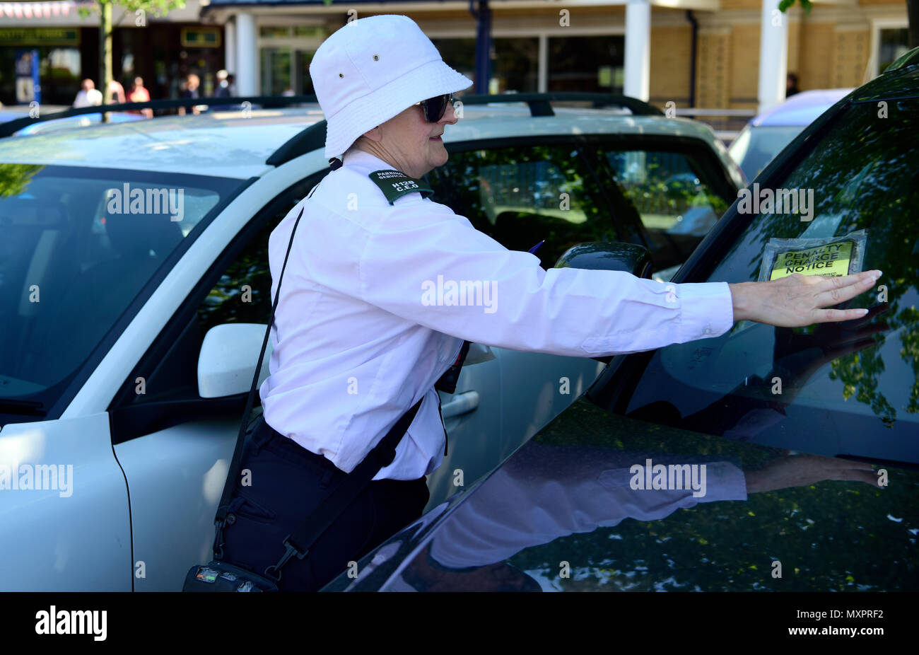 Car park enforcement officer placing Penalty Charge Notice on motorists car, Petersfield, Hampshire, UK. - Stock Image