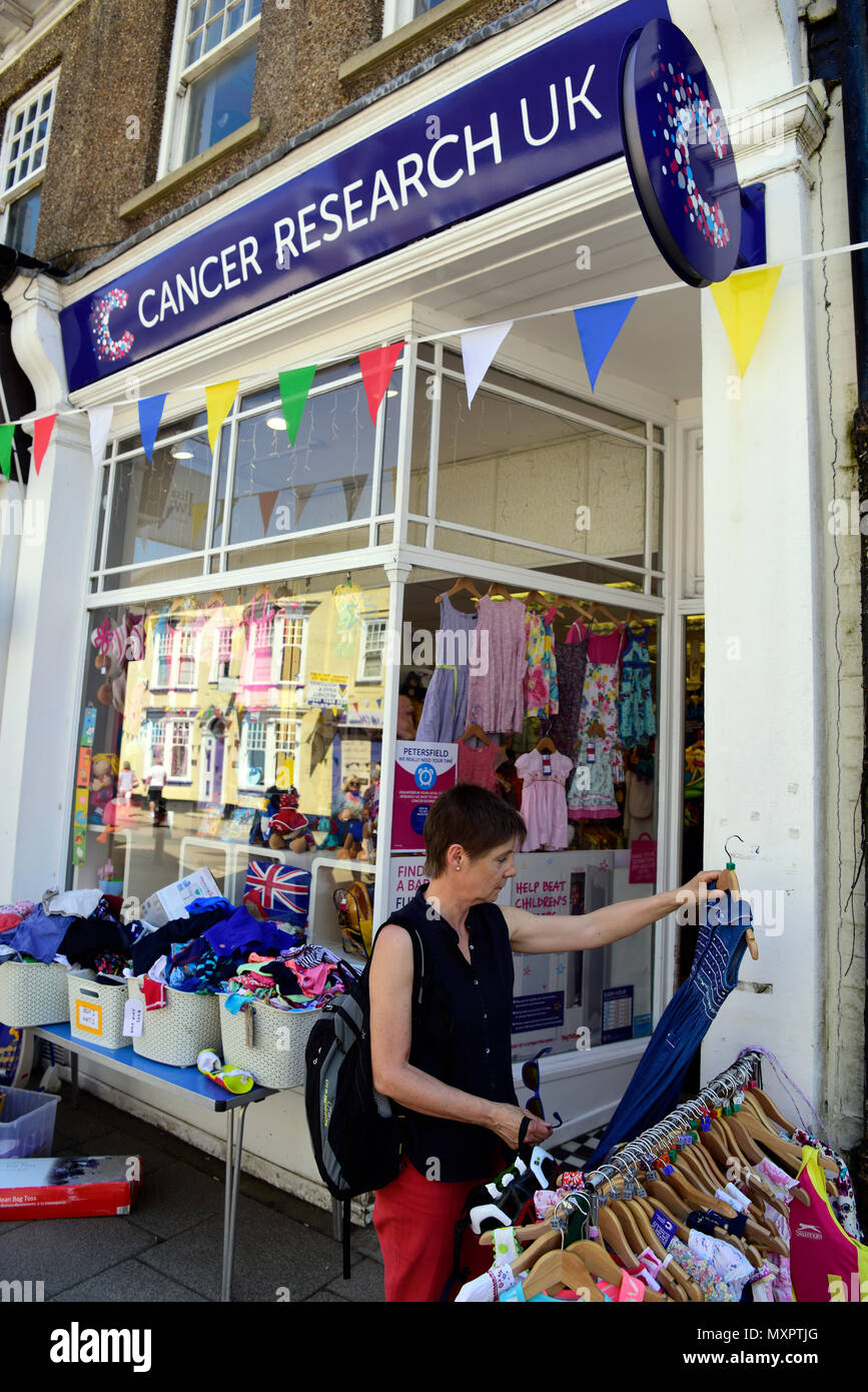 Woman browsing secondhand clothing section of Cancer Research UK charity shop, Petersfield, Hampshire, UK. - Stock Image