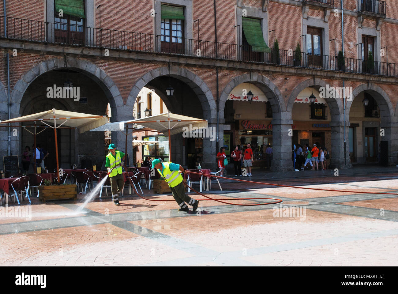 Street cleaners working at Mercado Chico Square. Avila, Spain. - Stock Image