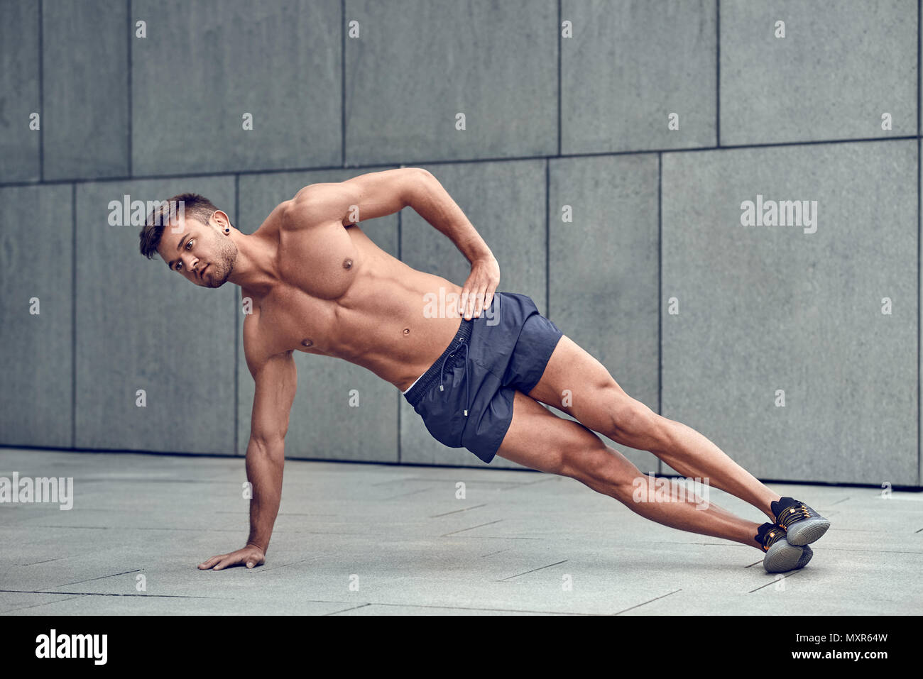 Fit healthy muscular young man with a bare chest doing side planks in an urban environment - Stock Image