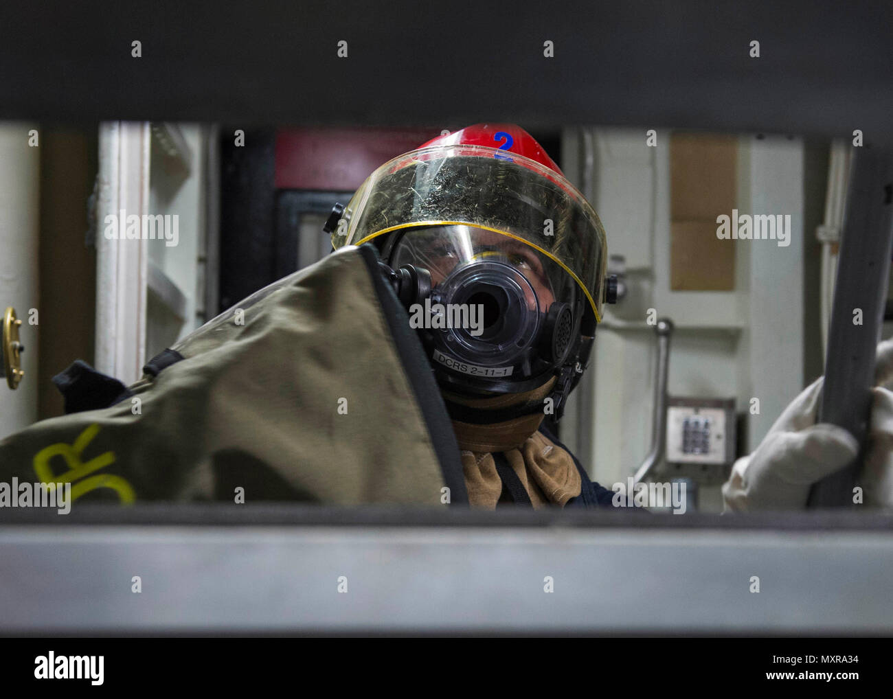 161128-N-XK398-088 PHILIPPINE SEA (November 28, 2016) Petty Officer 2nd Class Cole Ashdown inspects a compartment for potential hazards during a damage control drill aboard the Arleigh Burke-class guided-missile destroyer USS Mustin (DDG 89). Mustin is on patrol in the U.S. 7th Fleet area of responsibility in support of security and stability in the Indo-Asia-Pacific region. (U.S. Navy photo by Seaman Joshua Mortensen/Released) Stock Photo