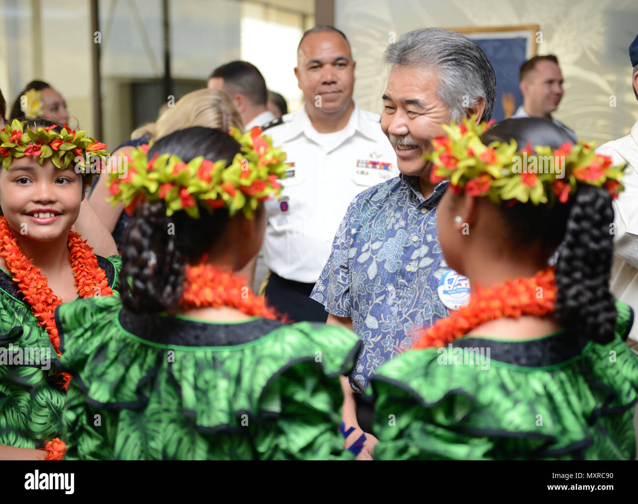 hawaii state governor david y ige speaks with several young girls