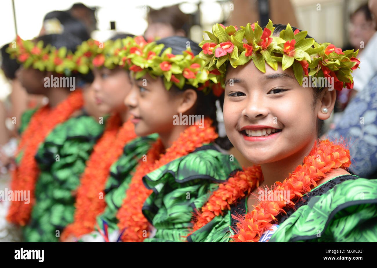 a young girl smiles before preparing to pass out flower leis during