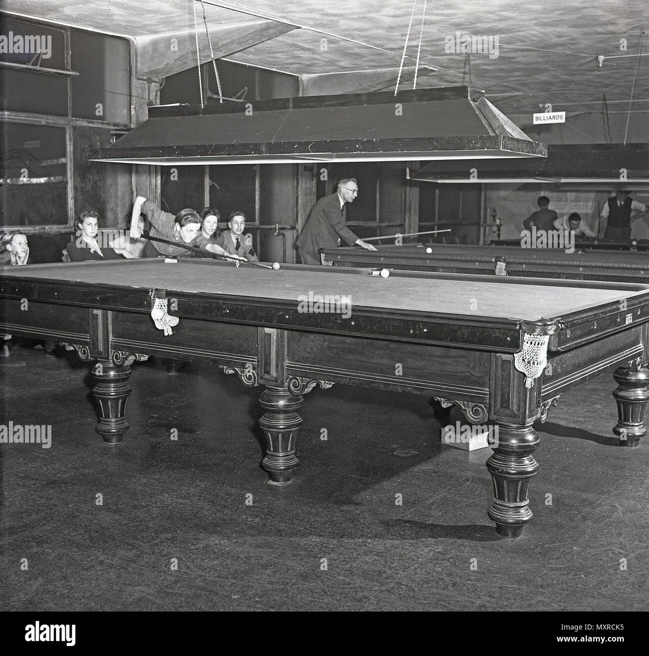 1948, historical, young people playing a game of billards or snooker in a snooker club, on a full-size table, England, UK. In this era, billards and/or snooker was a popular leisure activity but the pastime had limited appeal outside those who played it. Snooker, the so-called 'cue sport', originated among British Army officers stationed in India in the late 19th century. - Stock Image