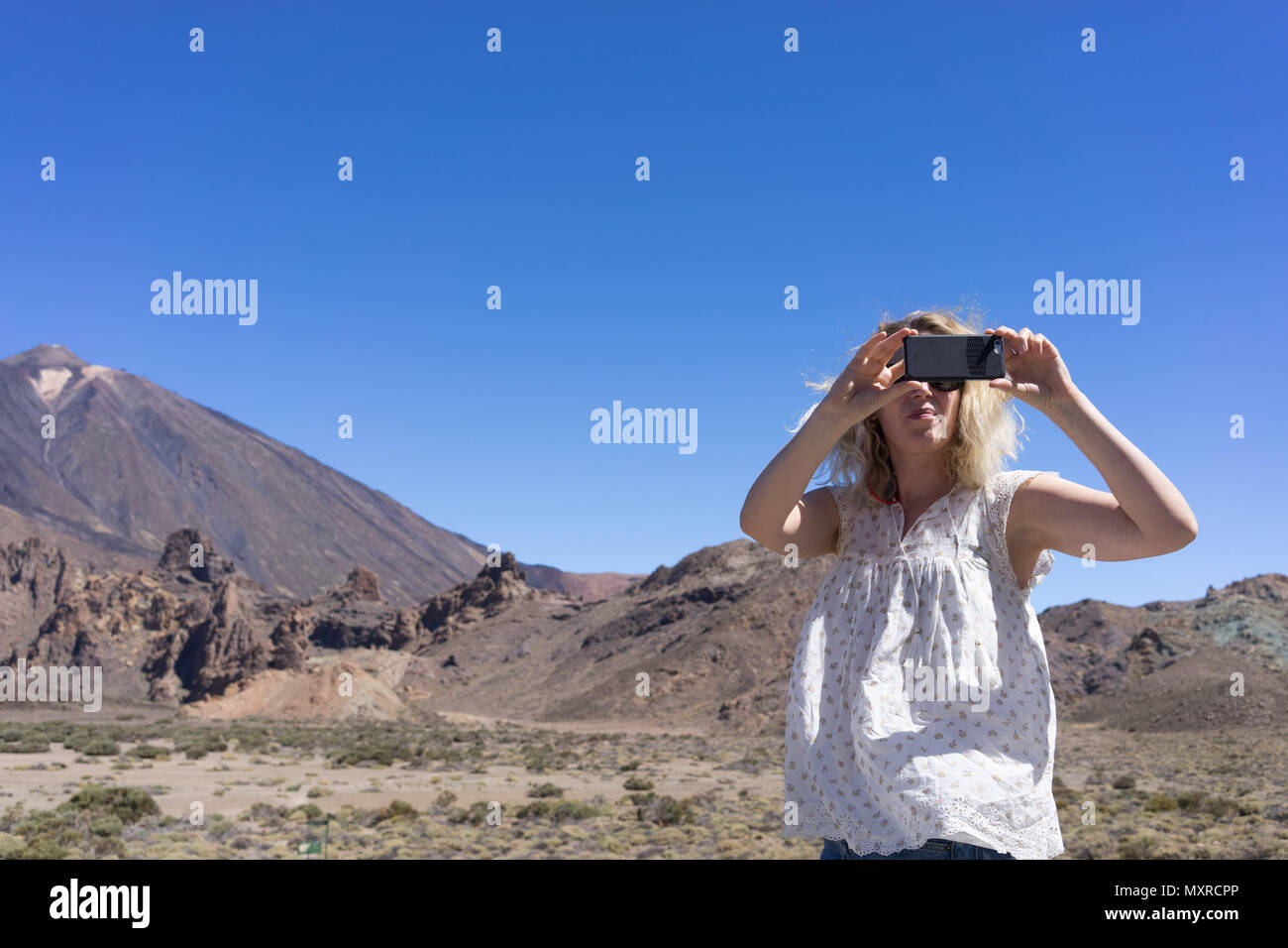 Woman taking a picture on her mobile phone with a volcano in the background - Stock Image