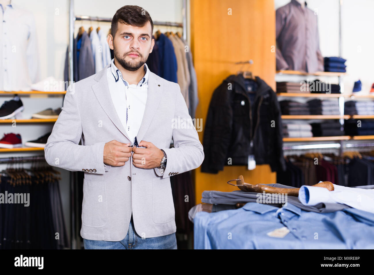 95e826f7 Smiling young male customer try new jacket in men clothes store ...
