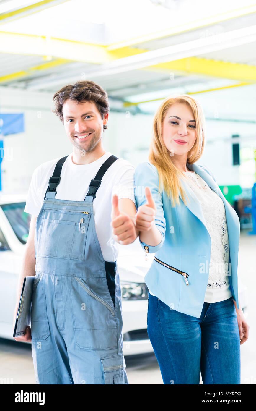 Workshop mechanic handing over car to client - Stock Image