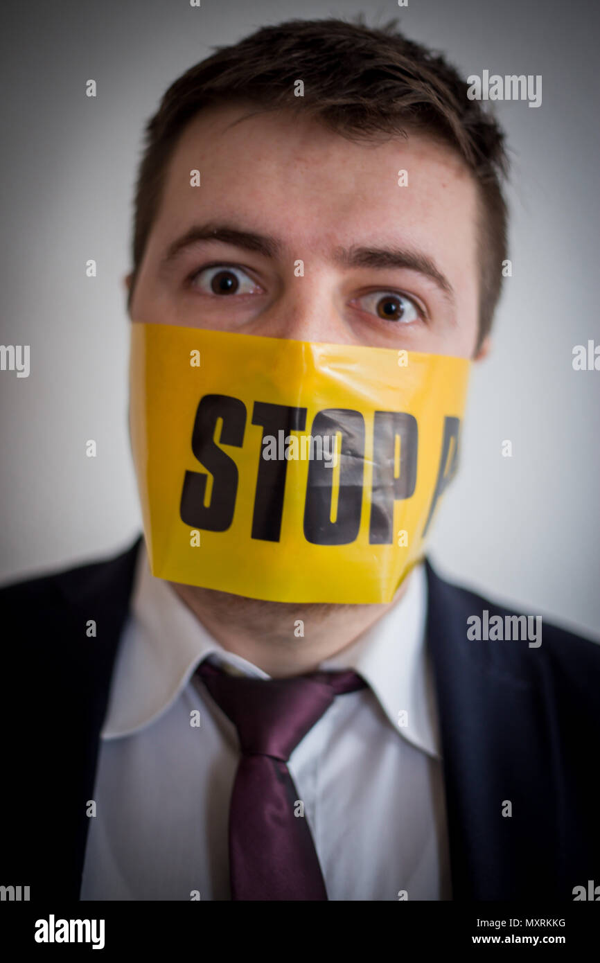 Businessman with a tie and suit surprised and worried for free speech violation yellow stop sign on his face and mouth covered and his eyes worried. - Stock Image