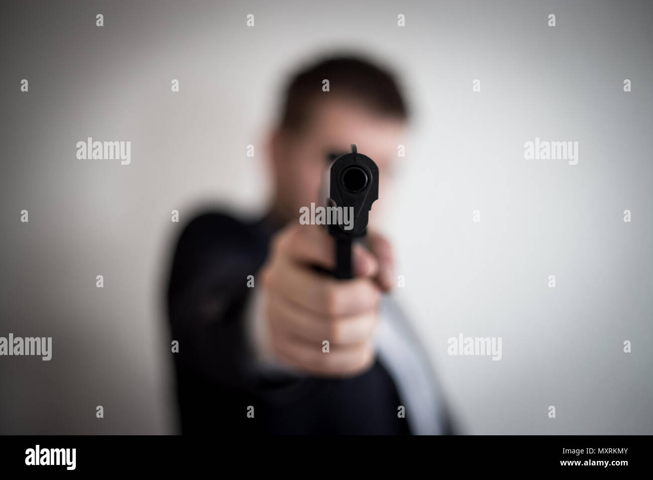A thief in a suit with a gun directed at a man takes cash, hundreds of dollars are abducted with the help of a pistol, a crime, an armed robbery - Stock Image