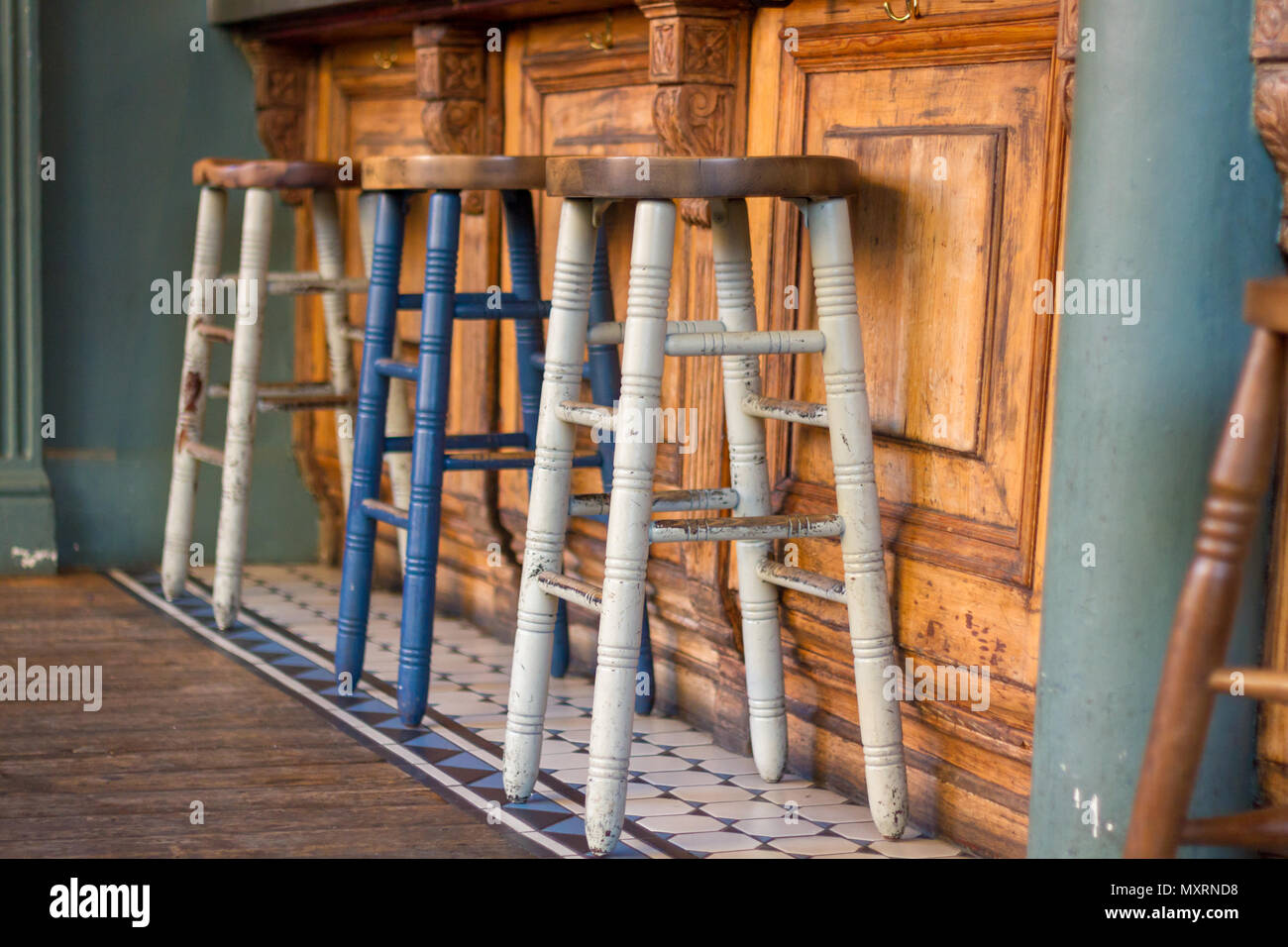 Painted Wooden Bar Stools In Front Of A Wooden Bar Stock Photo
