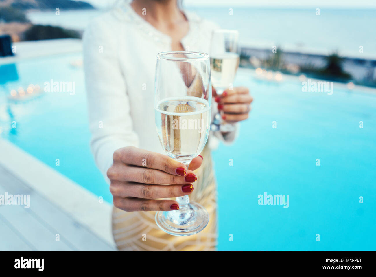 Woman handing glass of sparkling wine at pool and beach party - Stock Image