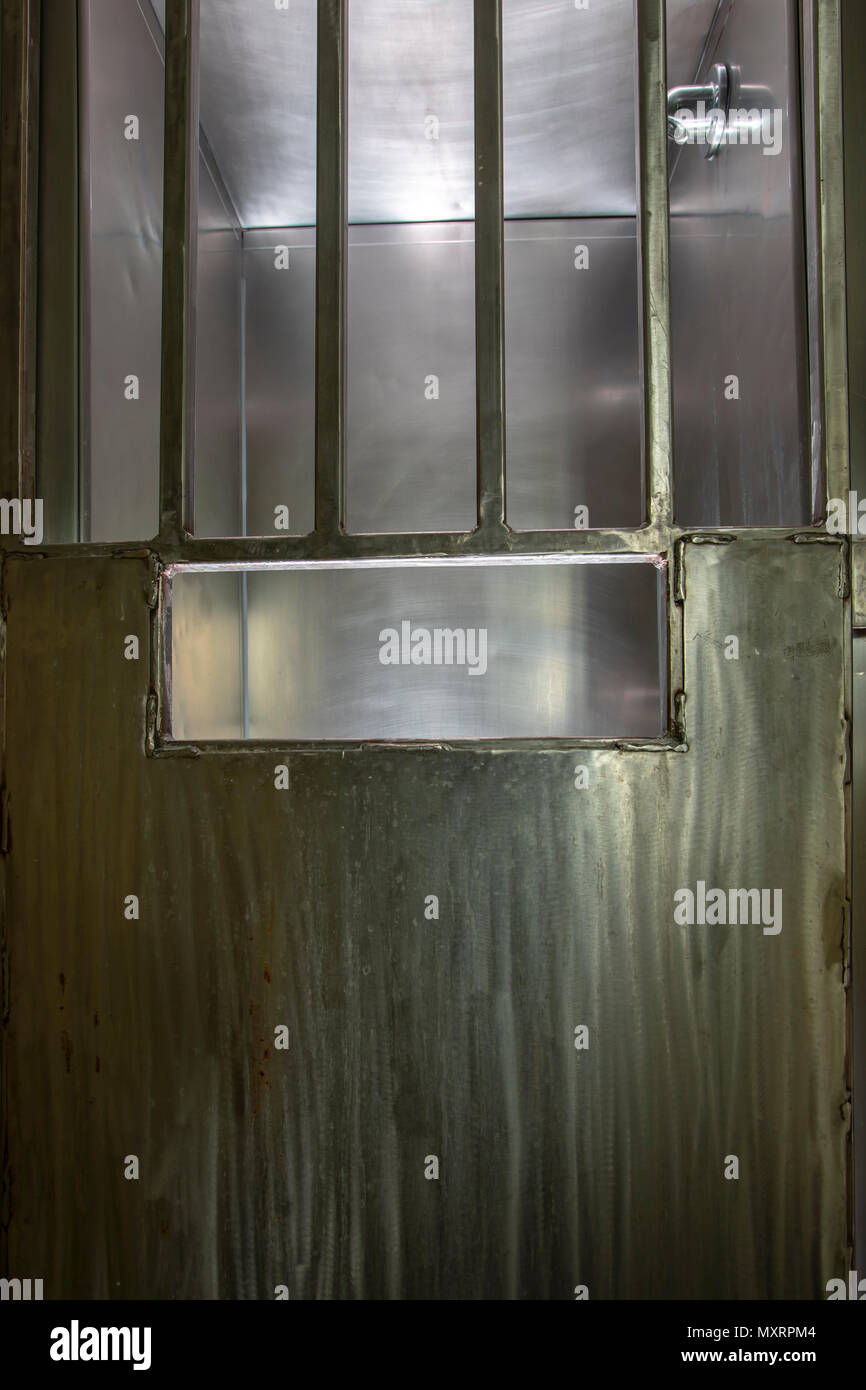 Steel door with bars on shower stall inside old prison hospital wing ...