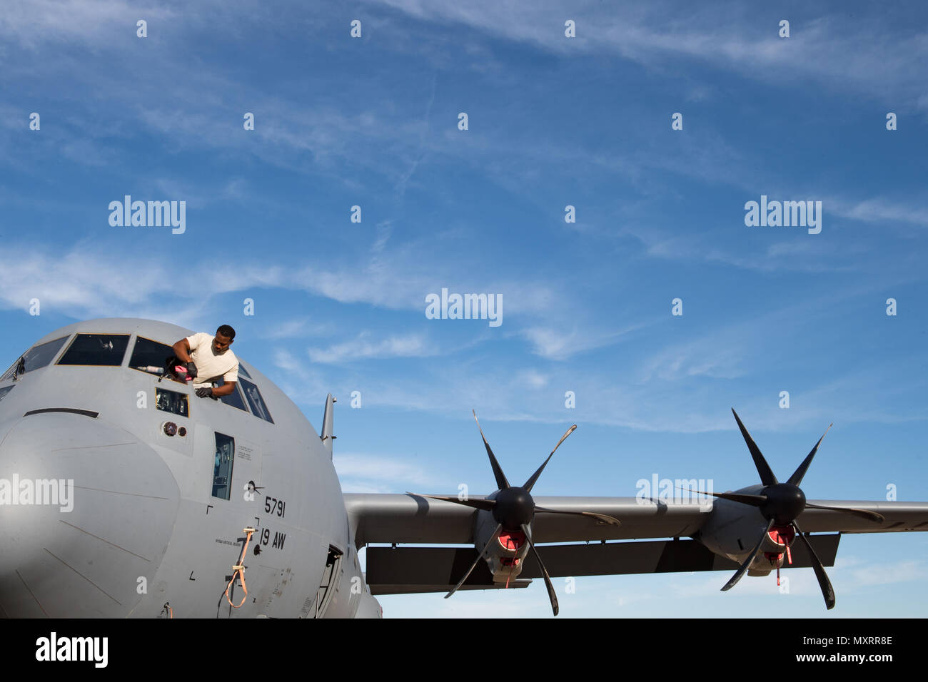 Airman 1st Class Dominick Partlow, a crewchief with the 19th Aircraft Maintenance Squadron at Little Rock Air Force Base in Arkansas, cleans the windows of a C-130J Hercules during a preflight inspection on November 21, 2016. Partlow, a native of Chapel Hill, N.C., is tasked with supporting the largest C-130 fleet in the world. (U.S. Air Force photo by Tech. Sgt. Brandon Shapiro) Stock Photo
