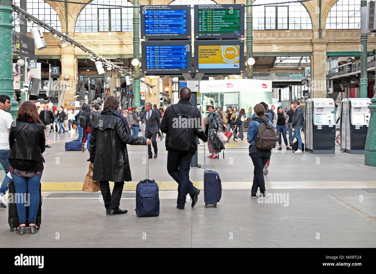 Interior view of passengers looking at departure and arrival screen on the concourse at the Gare du Nord in Paris France Europe  KATHY DEWITT - Stock Image