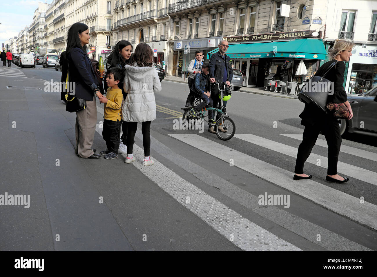Parents and children going home on an afternoon after the school day walking and on bike near a pedestrian crossing  in Paris France  KATHY DEWITT - Stock Image