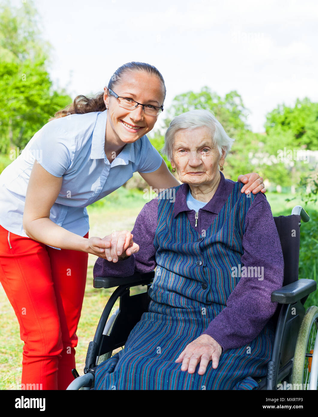 Handicapped elderly woman sitting in wheelchair with smiling caretaker outdoor - Stock Image