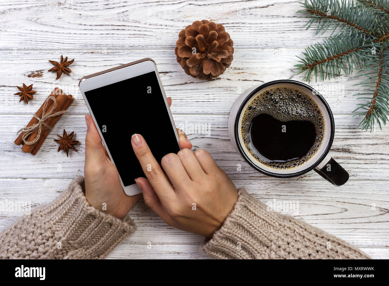 Girl in a cozy knitted sweater uses the phone while sitting at a table with Christmas accessories. - Stock Image