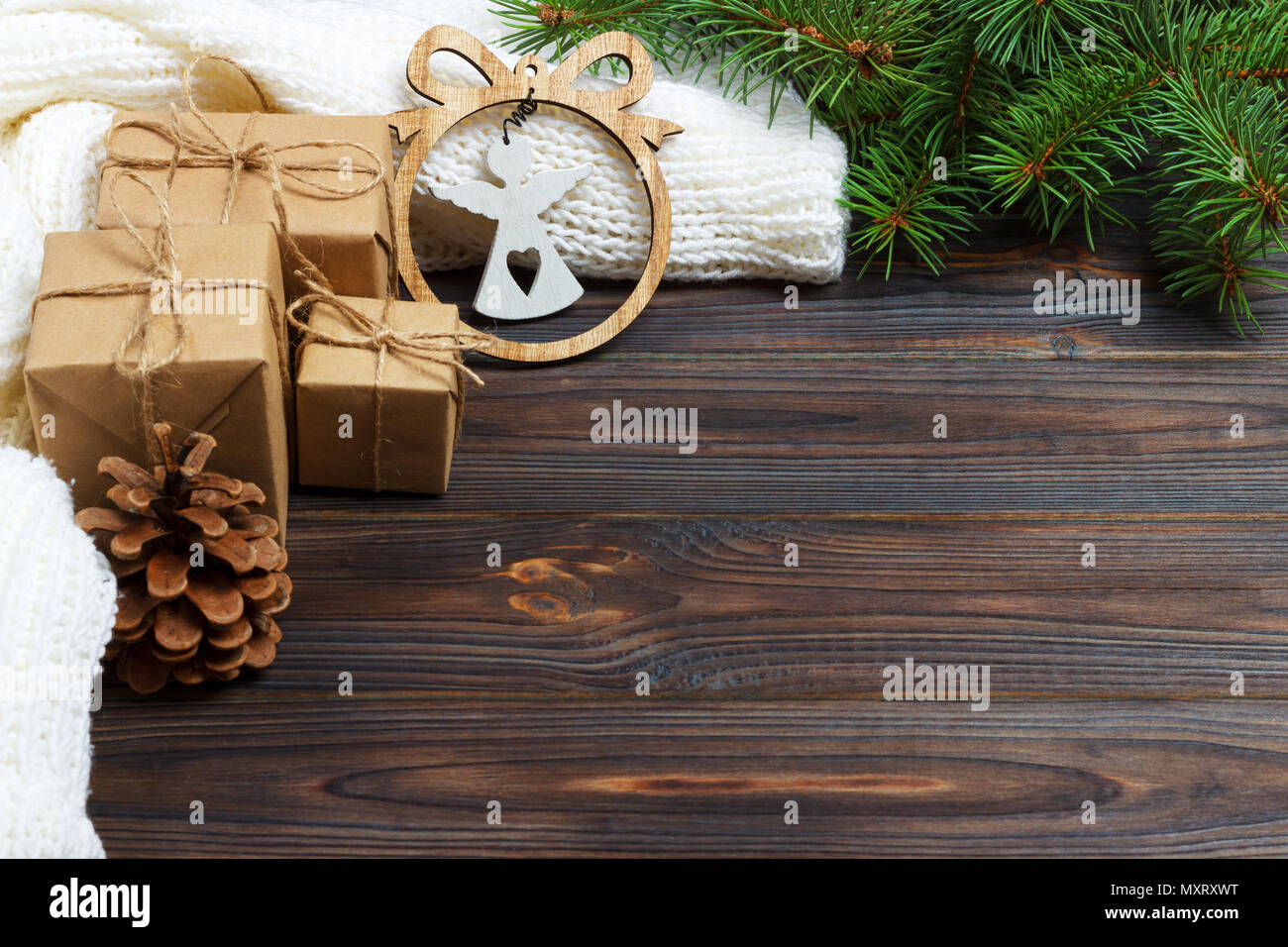 Wrapped christmas gifts with white angel on dark rustic wooden table