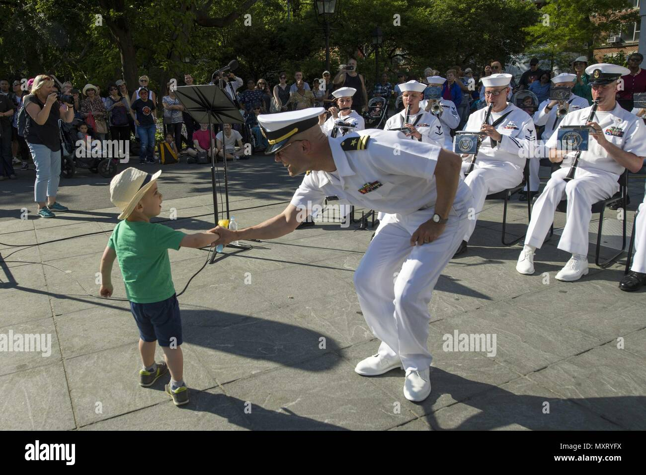 180524-N-BY095-0353 NEW YORK (May 24, 2018) Lt. Joel Borrelli-Boudreau shakes a young boy's hand during the Navy Band Northeast performance at Washington Square Park during Fleet Week New York (FWNY), May 24, 2018. Now in its 30th year FWNY is the city's time-honored celebration of the sea services. It is an unparalleled opportunity for the citizens of New York and the surrounding tri-state area to meet Sailors, Marines and Coast Guardsmen, as well as witness firsthand the latest capabilities of today's maritime services. (U.S. Navy photo by Mass Communication Specialist 3rd Class Maria I. Alv - Stock Image