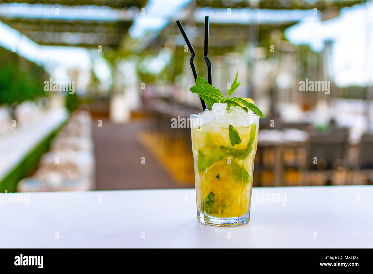 a chilled lime green mojito cocktail on a rooftop bar - Stock Image